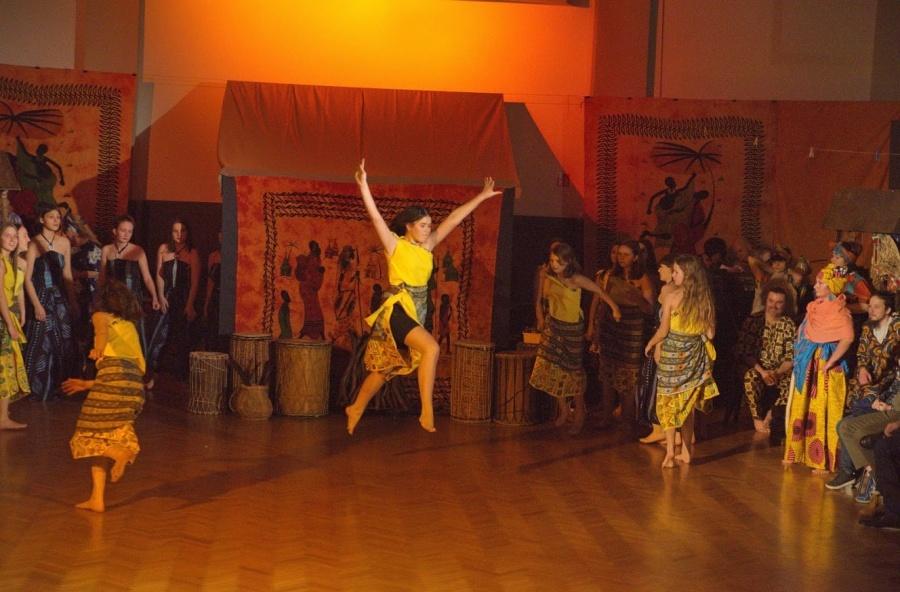 Dziewczyna w żółtej sukience w skoku z rękami uniesionymi do góry.