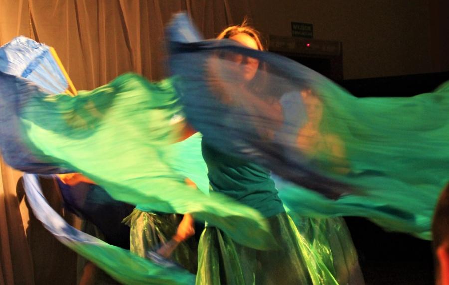 Kobieta tańcząca z rekwizytem wachlarzowoalem turkusowo-niebiesko-zielonym i imitującym wodę.