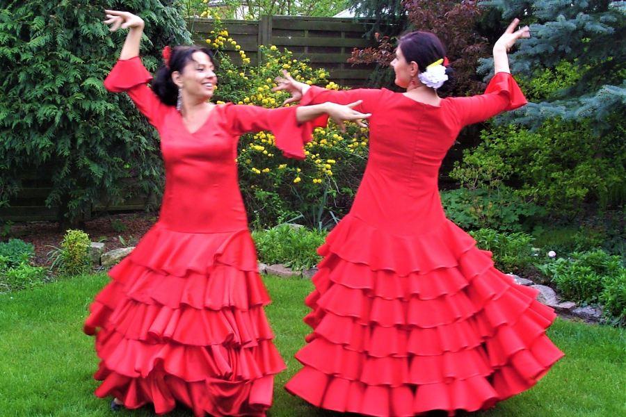 Dwie kobiety w czerwonych sukniach z falbanami na trawie w ogrodzie. Patrzą na siebie. Stoją w pozie tanecznej hiszpańskiego flameco