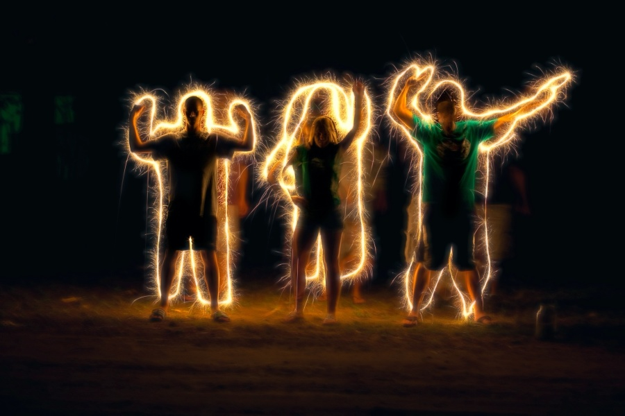 Zdjęcie przedstawia trzy osoby w żółtej poświacie. Ich kontury podświetlone odpowiednim światłem, zdają się być kimś z innego wymiaru.