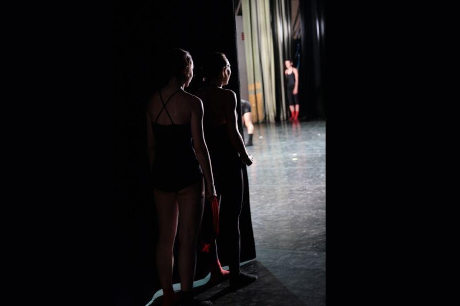 Zdjęcie zawiera obraz teatru zza kulis. Z tzw. bocznej kieszeni scenicznej, ( rodzaju wejścia z boku sceny ), stoją trzy osoby, które czekają na swoje wejście na scenę w odpowiednim dla nich momencie.