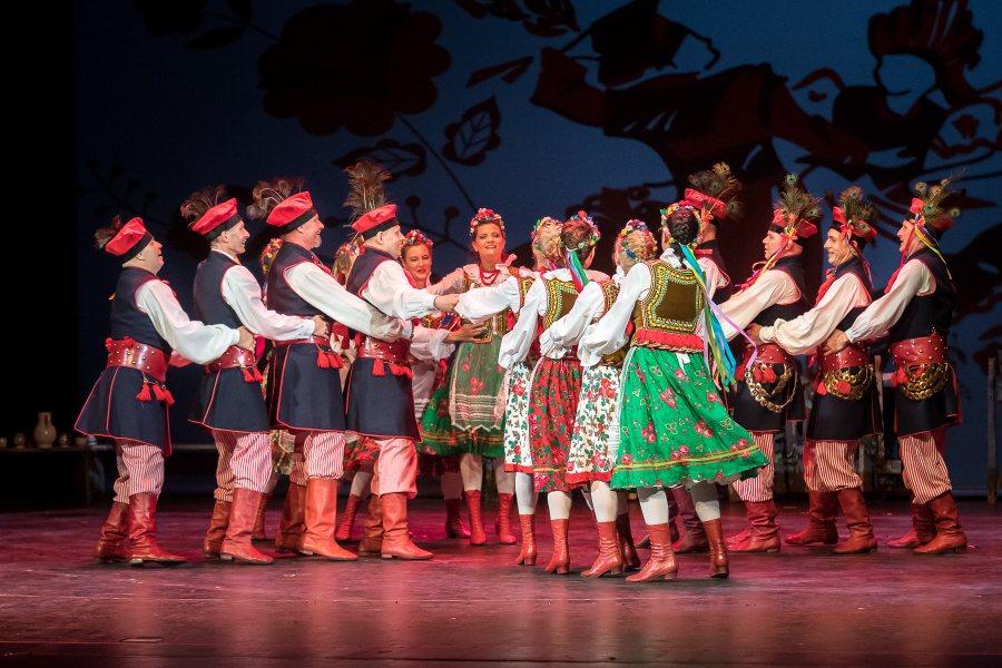 Pary tańczące krakowiaka w tradycyjnych strojach krakowskich.