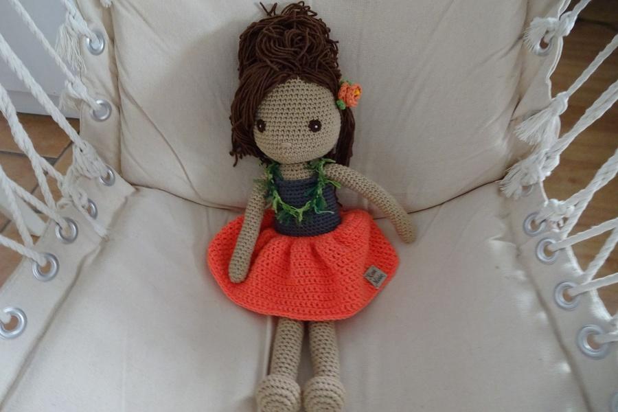 Szydełkowa lalka w pomarańczowej spódnicy, z hawajską girlandą na szyi i kwiatem we włosach siedzi na płóciennej huśtawce.