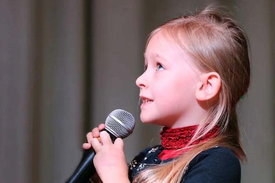 mała dziewczynka śpiewa do mikrofonu