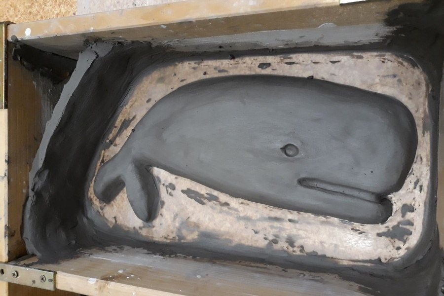 Gliniana płaskorzeźba w kształcie wieloryba leżąca w skrzynce