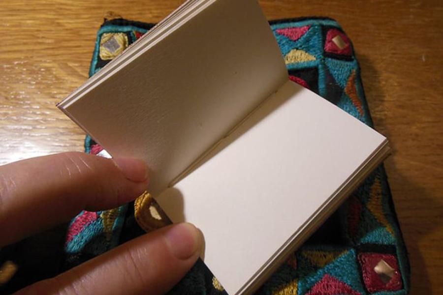 dłoń trzymająca mały notesik z białymi kartkami