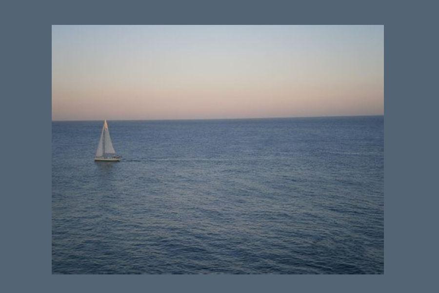 – spokojne morze, czysty horyzont i niebo o zmierzchu; w oddali jacht żaglowy.