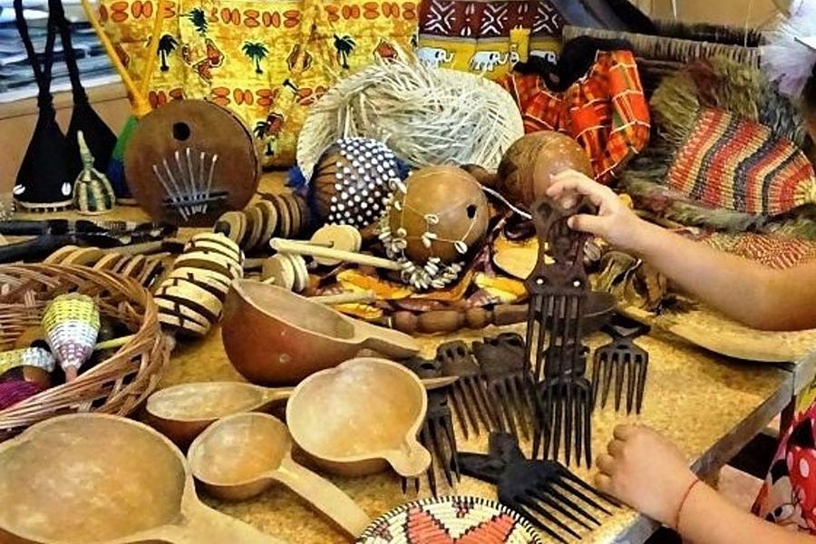 Przedmioty wykonane z naturalnych materiałów z Afryki( grzechotki, łyżki, grzebienie, torby) leżą na stole