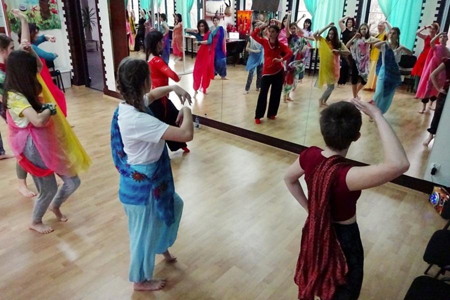 Grupa dziewcząt w kolorowych ubraniach z przewieszonymi chustami przez ramię w tanecznej pozie stoi przodem do lustra.