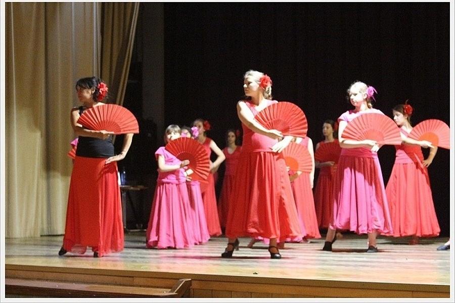 Grupa kobiet trzymająca czerwone wachlarze w tanecznej pozie na scenie.
