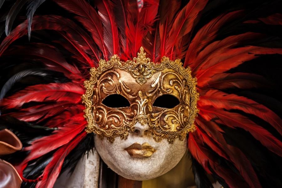 Maska wenecka o złotej i wzorzystej górnej połowie i białej dolnej połowie, złote usta, wokół maski wystające czerwone pióra, czarne tło