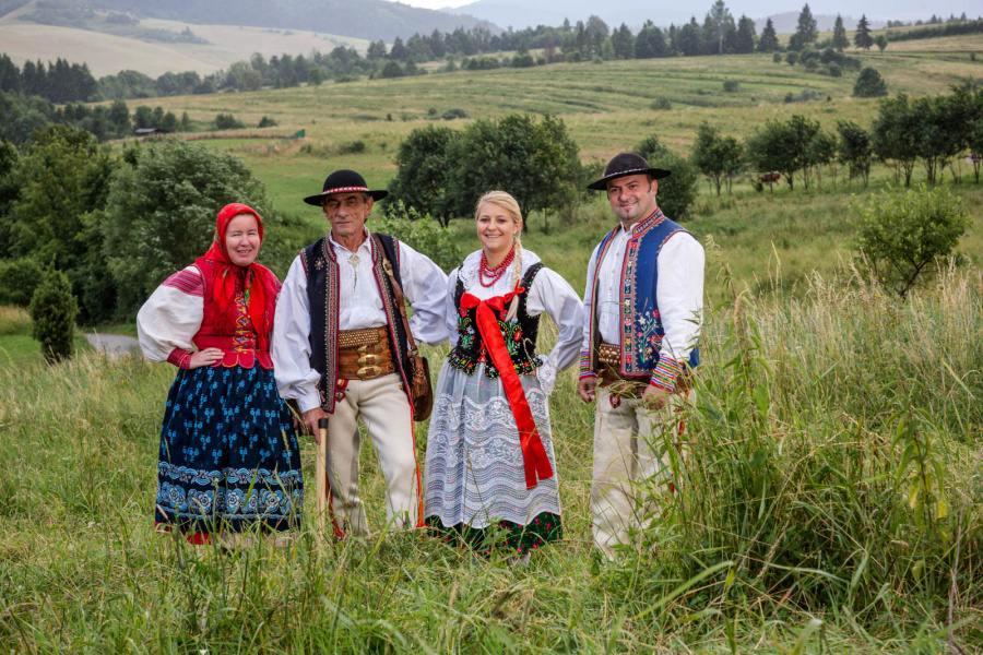Grupa ludzi w regionalnych strojach pienińskich stojąca na tle górskich łąk