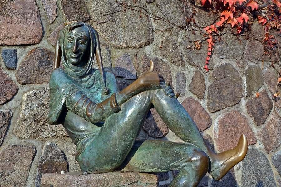 Rzeźba błazna w pozycji siedzącej na tle kamiennego muru