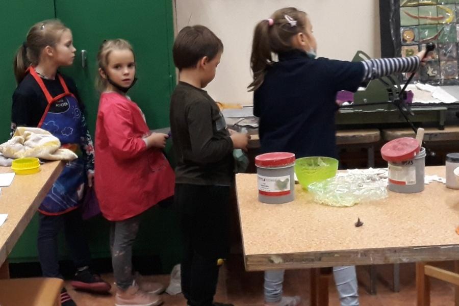 czworo dzieci stojących jedno za drugim prawym bokiem do widza na tle pomieszczenia.