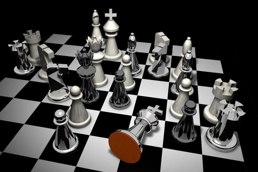 Błyszczące białe i czarne figury na szachownicy, z przewróconym czarnym królem