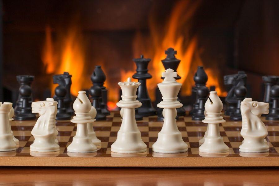 plansza z szachami na tle ognia płonacego w kominku