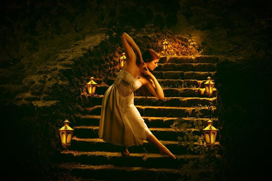 tancerka stojąca na schodach, po obu stronach zapalone lampy