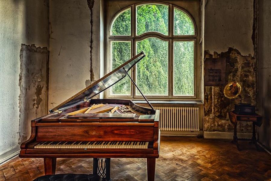 fortepian sotjący na środku zniszczonego pokoju