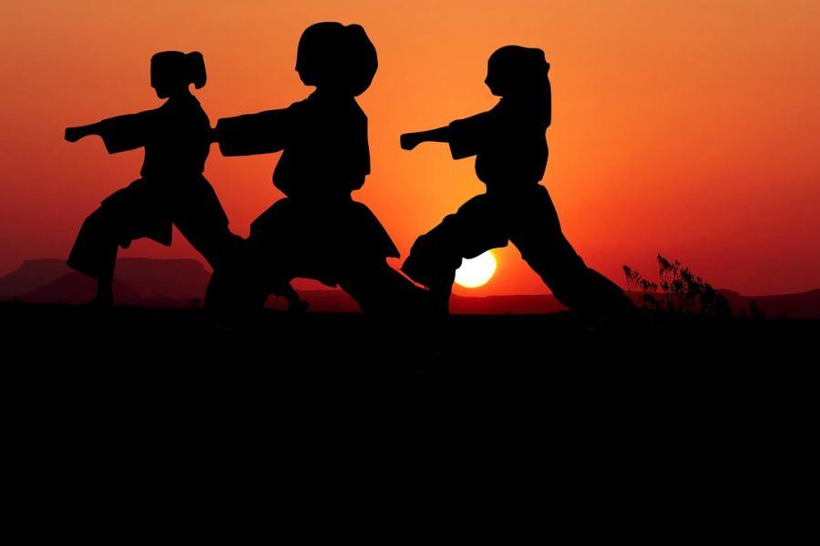 trzy postacie karateków na tle zachodzącego słońca