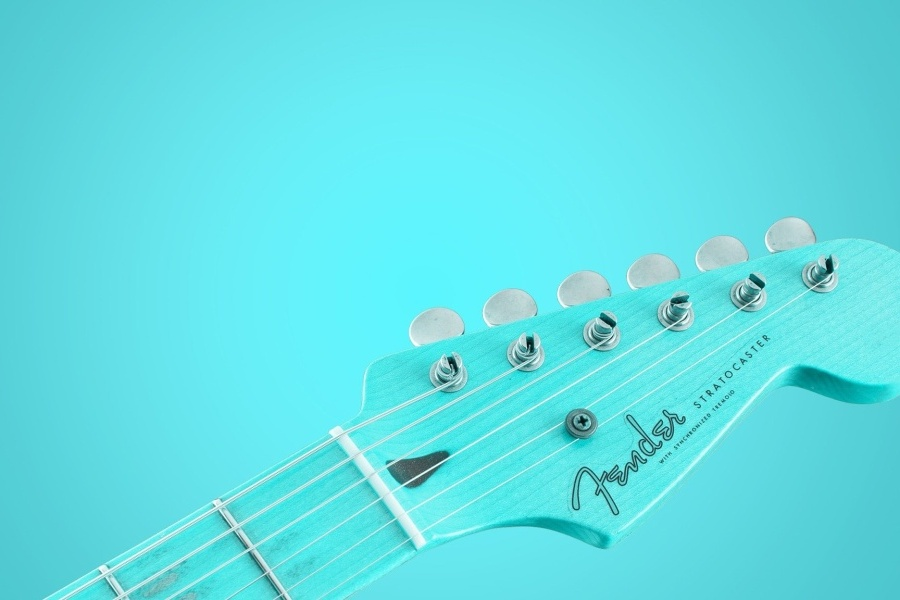 Niebieska główka gitary elektrycznej na błękitnym tle