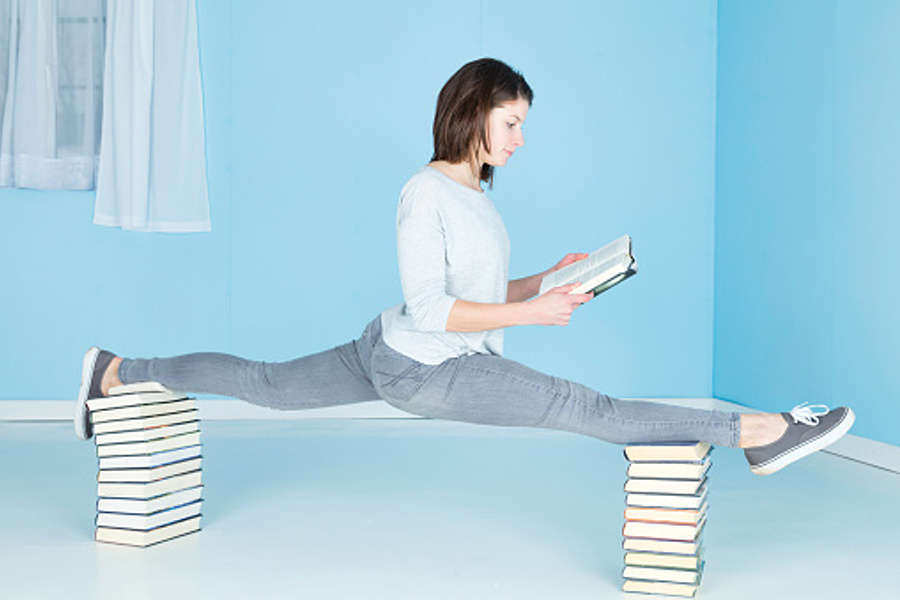 młoda dziewczyna robiąca szpagat na ksiazkach