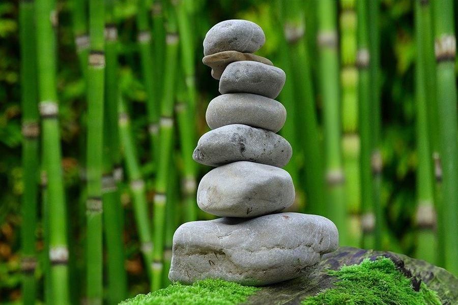 na zdjęciu znajdują się szare kamienie ułożone jedne na drugim w formie wieży. w tle zielone łodygi bambusa.