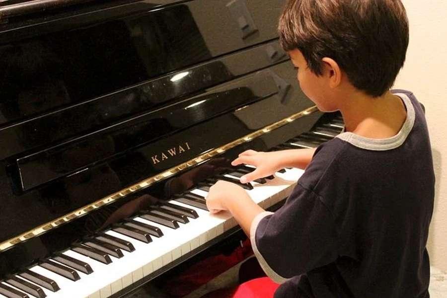 Na zdjęciu chłopiec gra na fortepianie mark Kawai.