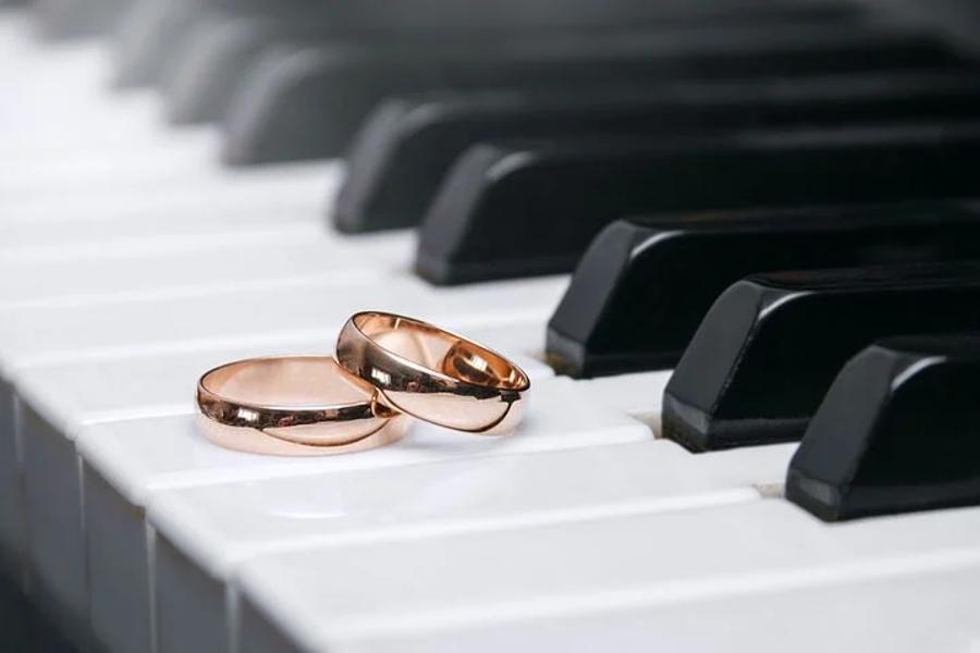 klawisze fortepianu a na nich dwie złote obrączki