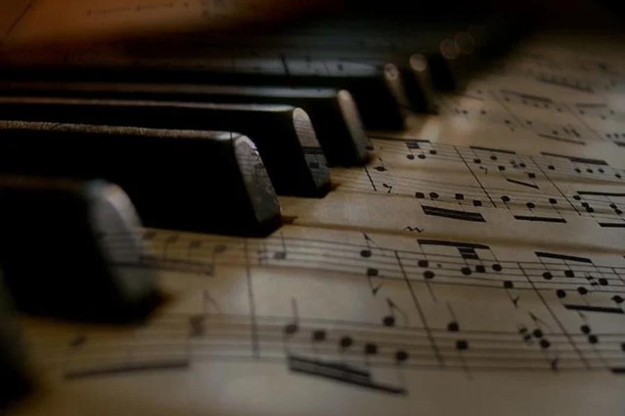 Na zdjęciu widać klawiaturę fortepianu całą pokrytą nutami.