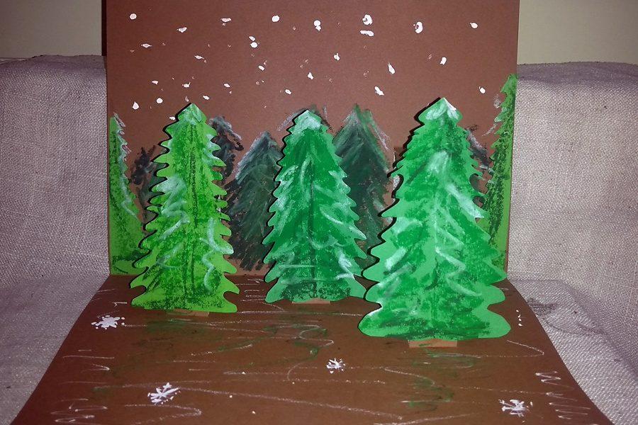 zielone papierowe choinki na brązowym tle -praca plastyczna przestrzenna