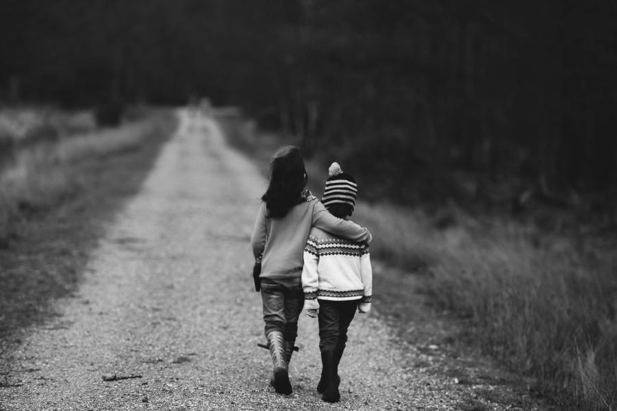 czarno-biała fotografia z dwójką dzieci idących drogą