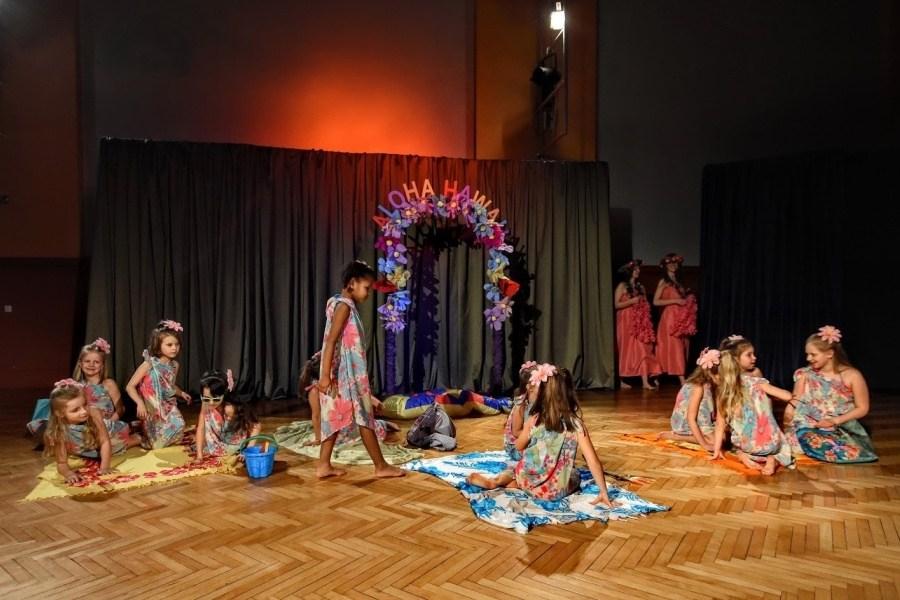 Grupa dzieci ubrana w kolorowe parea siedzi i stoi na scenie. W tle dekoracja z napisem Aloha Hawaje.