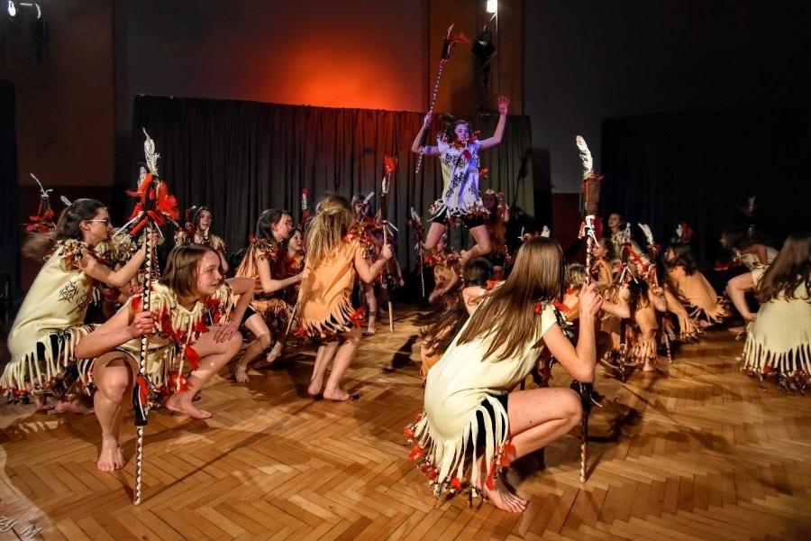 Grupa dziewcząt w pomarańczowych i kremowych tunikach z czerwono-czarnymi piórkami tańczą na scenie z włóczniami w rękach.