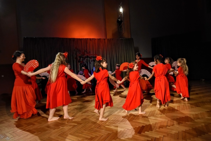 Grupa dziewcząt ubranych w czerwone suknie tańczy w kole trzymając wachlarze w kropki.