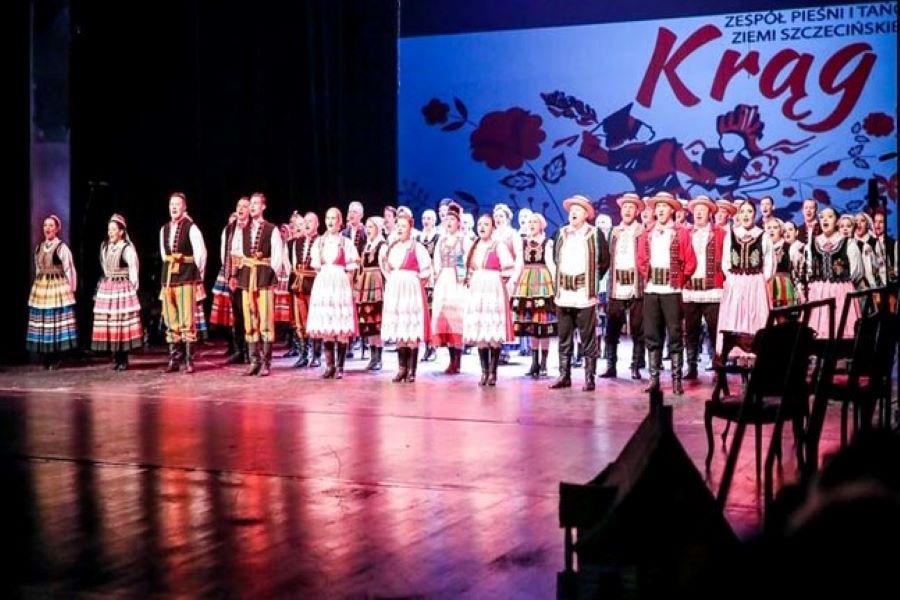 grupa ludzi w strojach ludowych stojących na scenie