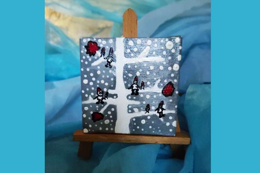 mały obraz na małej sztaludze przedstawia: na szaroniebieskim tle wypełnionym białymi kropkami centralnie stoi białe drzewko ; na gałęziach siedzą małe ludziki w czerwonych czapeczkach