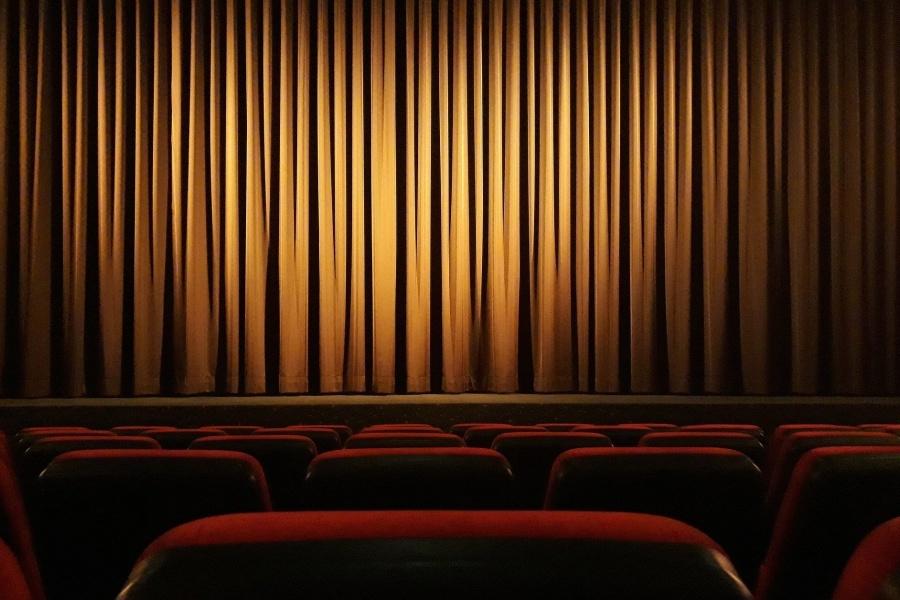 Widownia teatralna z widocznymi czerwonymi krzesłami i jasnobrązową kurtyną spuszczoną na scenę