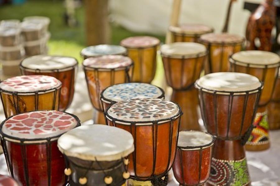 """Zdjęcie przedstawia wiele ręcznie wykonanych afrykańskich bębnów """"djembe""""."""