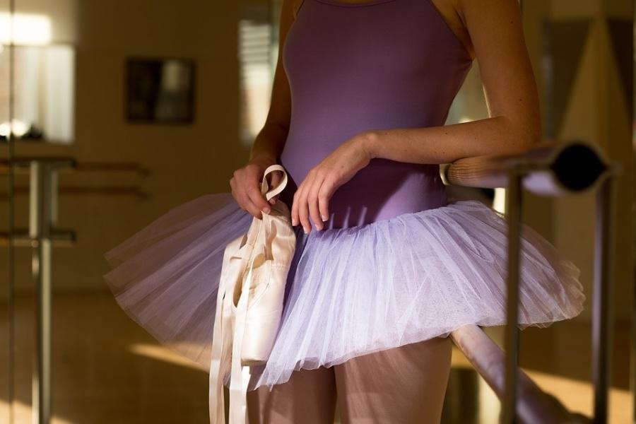 Zdjęcie przedstawia połowę sylwetki tancerki stojącej przy drążku w fioletowym kostiumie, trzymającej w ręku pointy.