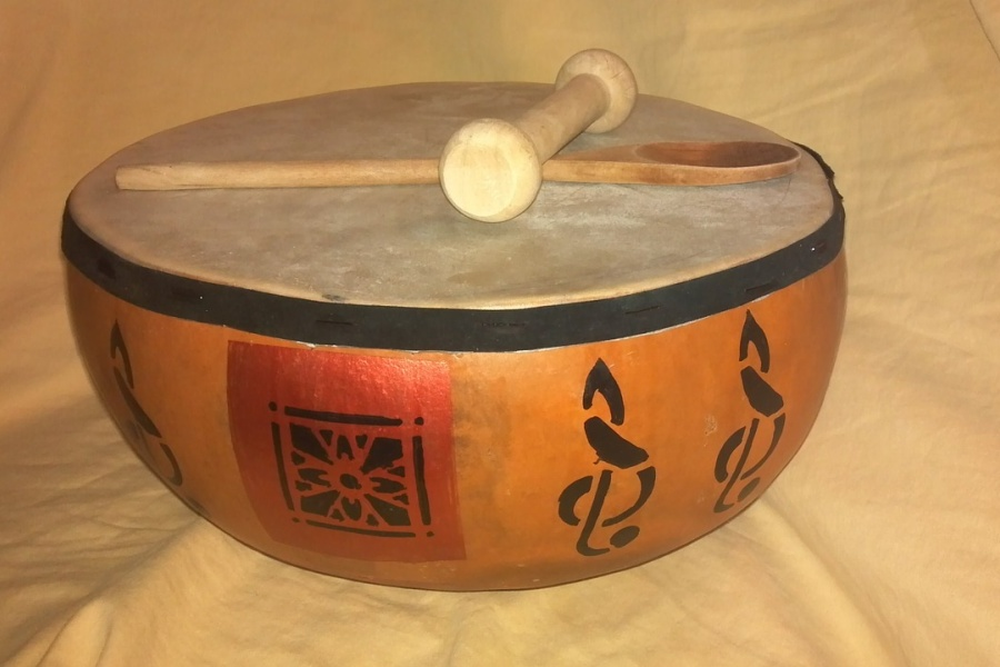 Zdjęcie przedstawia etniczny instrument perkusyjny a na nim położone drewniana łyżka oraz tłuczek