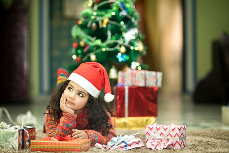 dziewczynka w czapce mikołaja leżaca pod choinką, w tle choinka i prezent