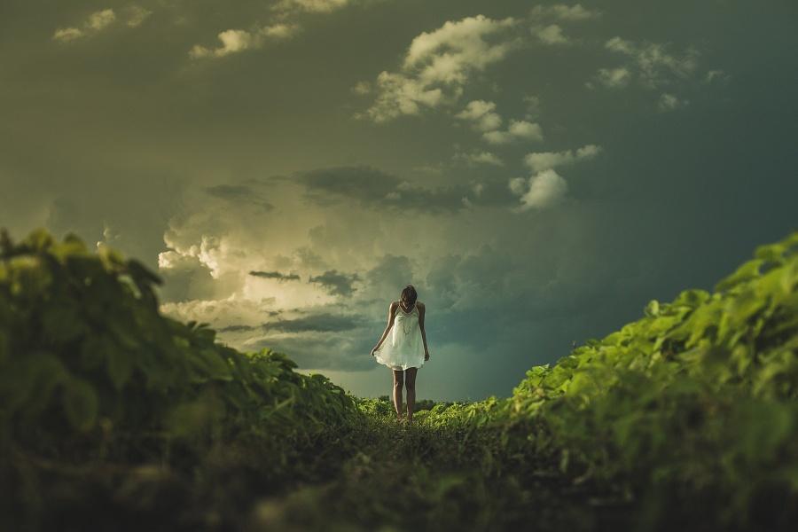 Zdjęcie przedstawia kobietę stojącą na zielonej trawie, na tle nieba.