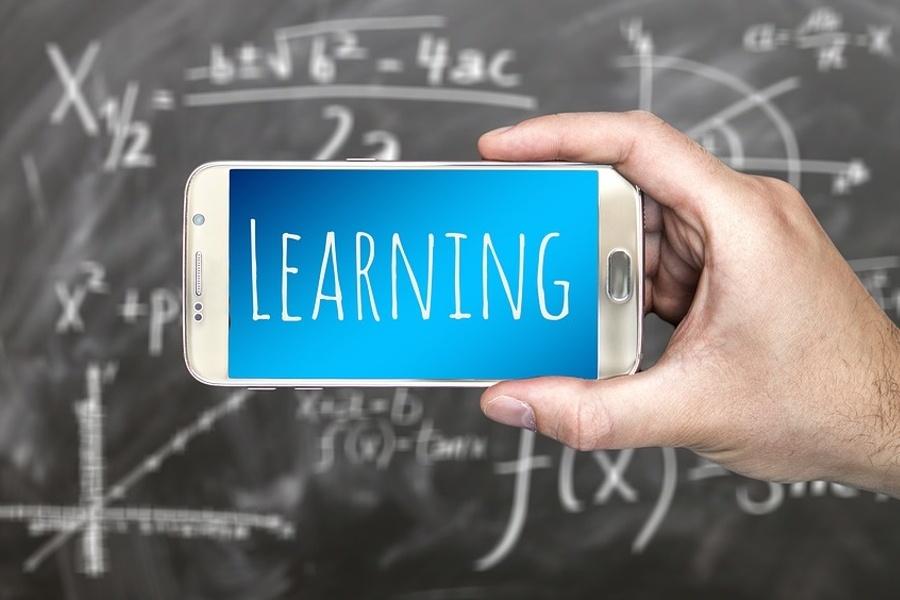 Na zdjęciu smartfon z napisem nauka, w tle tablica szkolna