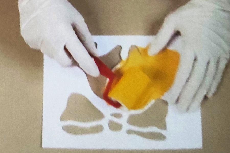 szablon z symbolicznymi elementami świątecznymi i proces odbijania stencilu do realizacji na pudełku