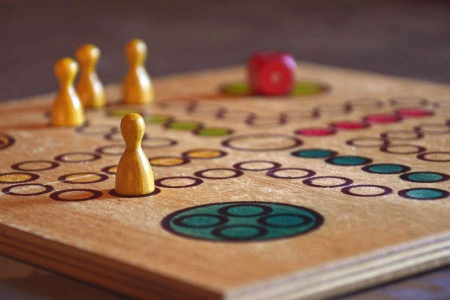 żółte pionki na drewnianej planszy do gry