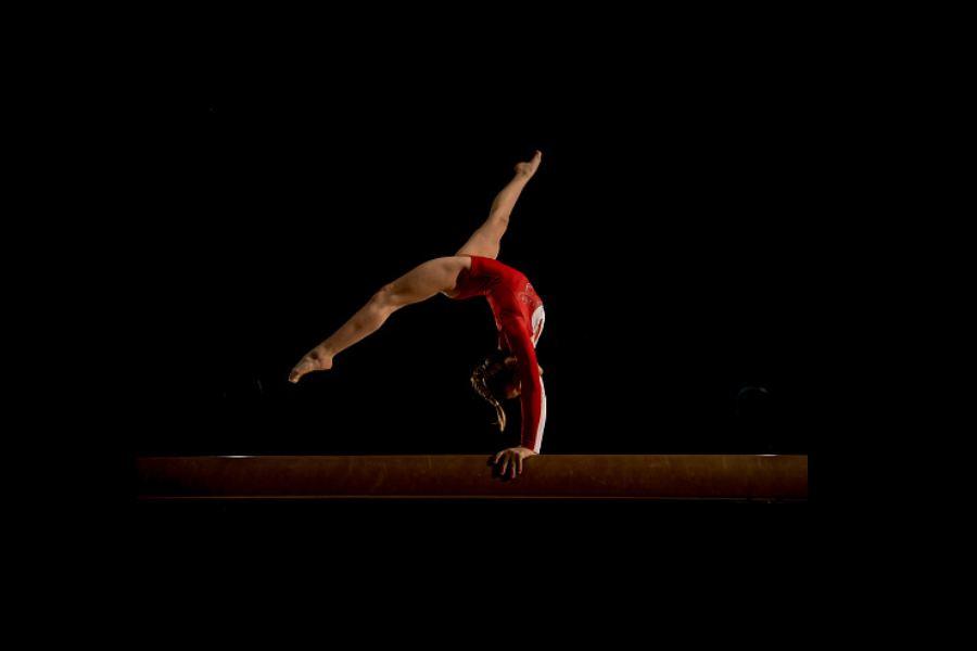 gimnastyczka w czerwonym stroju robi przejście akrobatyczne w przód