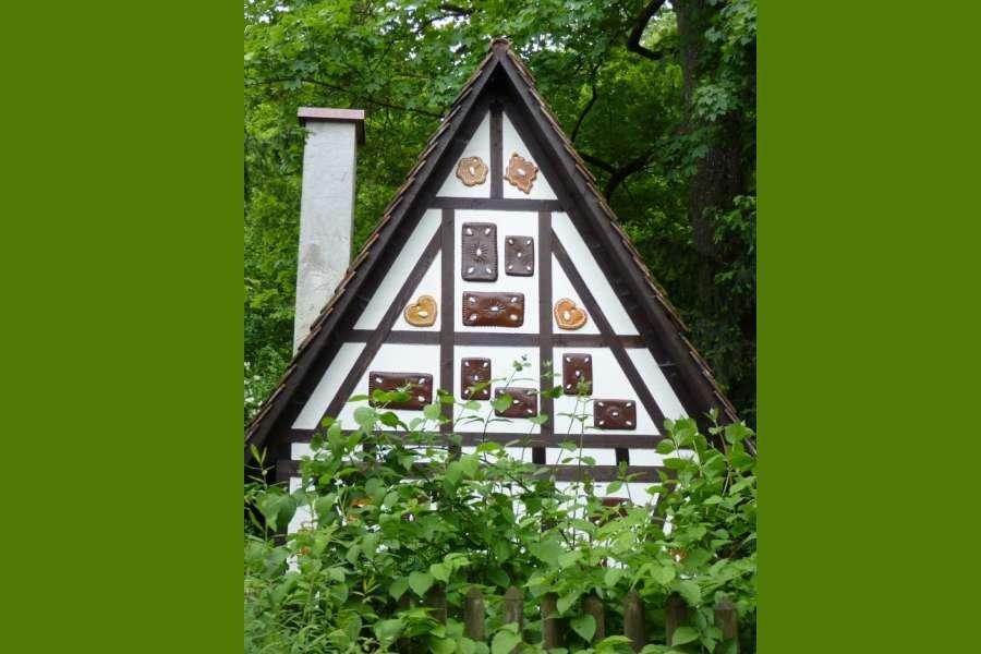 Zdjęcie przedstawia biały domek w piernikach w otoczeniu zieleni.
