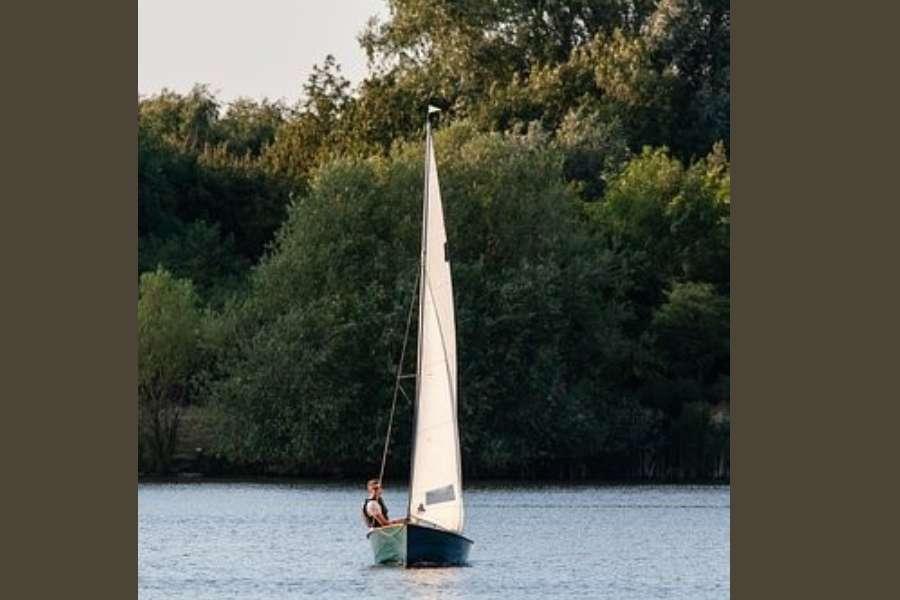 Żeglarz na małej łódce płynący na tle zalesionego brzegu
