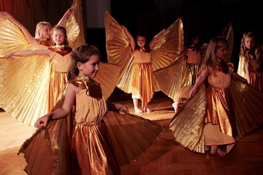 Grupa dziewcząt ubranych w złote kostiumy ze złotymi skrzydłami stoi na scenie w tanecznej pozie.