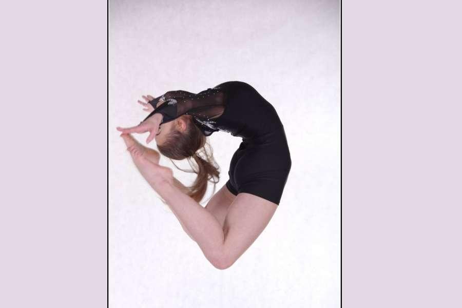 tancerka w czarnym kostiumie, wykonująca skok tzw. kółeczko
